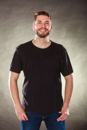 male  man: Portrait of happy handsome fashionable man in black blank shirt with empty copy space. Young guy in studio on black. Casual fashion advertisement.