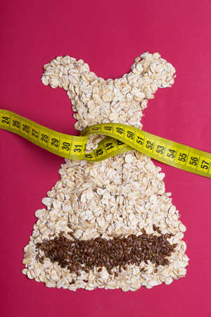 waist down: Dieting healthy eating slim down concept. Female dress shape made from oatmeal flax seeds with measuring tape around thin waist on red