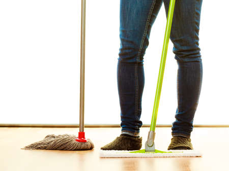 mops: Cleanup housework concept. Cleaning woman legs, girl mopping floor, holding two mops new and old white background