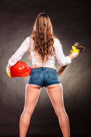alluring: Sexy alluring woman holding axe chopper and helmet. Strong girl feminist working in man profession. Independent female. Rear view.