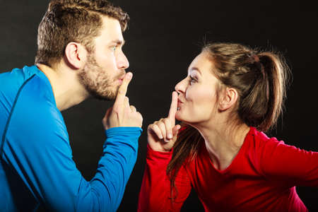 mouth couple: Couple asking for silence with finger on lips mouth gesture. Quiet man and woman in studio on black.