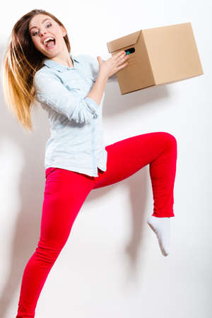 Happy woman moving in carrying carton box. Young girl arranging interior and unpacking at new apartment house home.