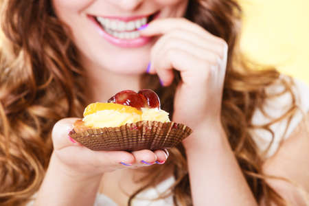 flirty: Sweetness and happiness concept. Closeup cute flirty woman eating fruit cake licks fingers yellow background
