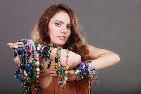 pietre preziose: Piuttosto giovane donna che indossa bracciali e anelli azienda molti abbondante di gioielli preziosi collane perline. Ritratto di splendida ragazza di moda in studio su grigio.