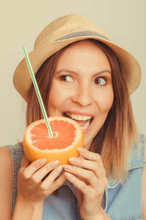 summer diet: Happy glad woman tourist in straw hat eating biting grapefruit citrus fruit. Healthy diet food. Summer vacation holidays concept. Instagram filtered.