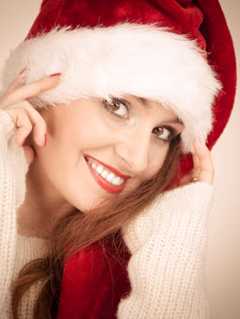 sweater girl: Christmas time. Young latin woman wearing santa claus hat white warm sweater portrait. Studio shot.