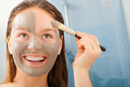 facial: Beauty procedures skin care concept. Young woman applying facial gray mud clay mask to her face in bathroom