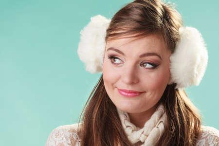 Earmuffs: Portrait of smiling cute pretty woman in earmuffs. Happy lovely girl in studio on green. Stock Photo