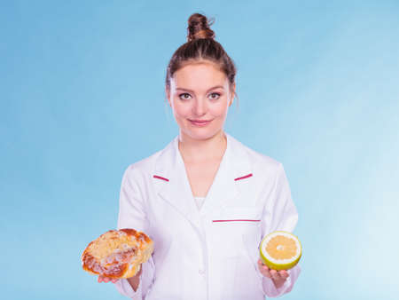 eating right: Dietitian nutritionist with sweet roll bun and grapefruit. Woman holding fruit and cake comparing junk and healthy food. Right eating nutrition concept. Stock Photo
