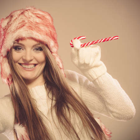 sweater girl: Young woman playing with cane and mug. Girls hands in woolen white gloves having fun. Christmas time concept.