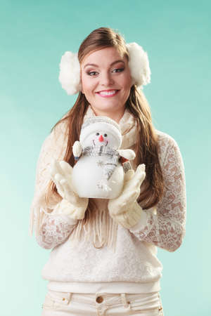 sweater girl: Smiling pretty cute woman holding little snowman. Attractive girl in earmuffs and white sweater pullover in studio on green. Winter fashion. Stock Photo