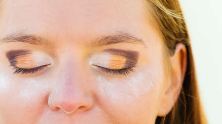 eyelids: Makeup and cosmetics. Part of woman face, female eyes with eyeshadow, stage of applying make up on eyelids