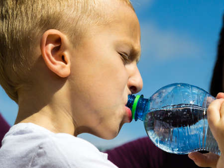 water park: Little thirsty boy child drink water from plastic bottle, outdoor Stock Photo