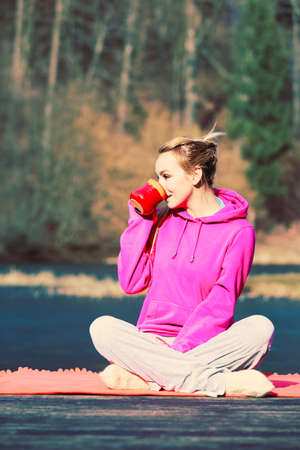 care about the health: Young pretty girl at park drinking hot tea in mug. Woman care about health sitting on fresh air. Stock Photo
