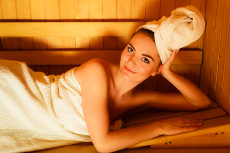 sauna: Spa beauty well being and resort concept. Woman in full length white towel lying relaxed in wooden finnish sauna Stock Photo