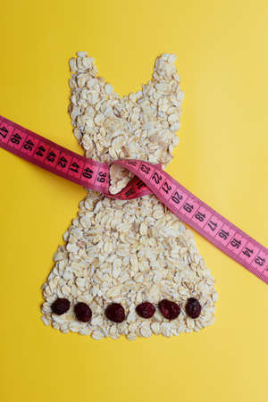 waist down: Dieting healthy eating slim down concept. Female dress shape made from oatmeal dried fruit with measuring tape around thin waist on yellow Stock Photo