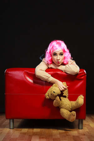 girl doll: Mental disorder concept. Young childlike woman wearing like puppet doll sitting with teddy bear toy on red couch dark black background