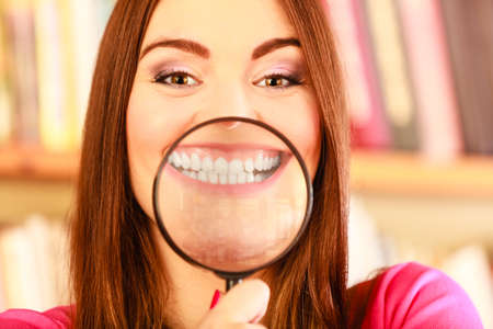 lupa: exploration education or dental care concept. Closeup funny smiling woman face, girl holding on lips magnifying glass loupe showing teeth
