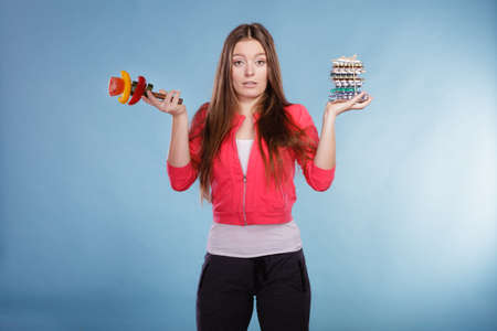 WEIGHT: Woman girl holding diet weight loss tablets pills and vegetables. Choice between natural and synthetic way of slimming dieting. Health care. Stock Photo