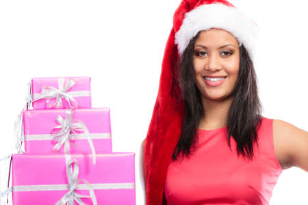 multiple ethnicity: Christmas winter happiness concept. Girl mixed race woman wearing red dress santa helper hat holding stack of pink presents gift boxes on white