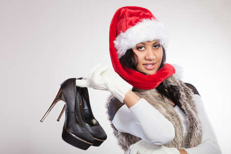 gorgeous woman: Fashion mixed race african american woman in santa claus hat holding black high heels shoes. Gorgeous young girl in studio on gray. Female fashion.