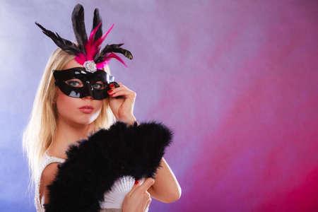 femme blonde: Vacances, les gens et concept c�l�bration. visage de femme Gros plan caucasien fille blonde noir rose masque de carnaval, tenant �ventail de plumes dans la main