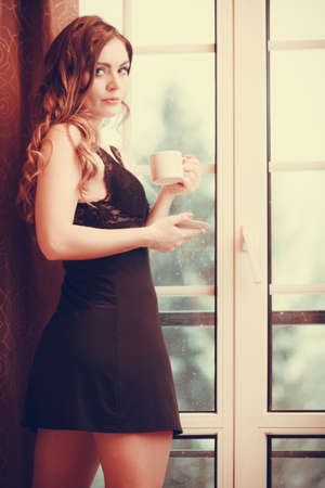energizing: Sensual seductive woman in lingerie drinking cup of coffee by curtain and french door window at home. Young girl with hot energizing beverage stay awake. Caffeine energy. Instagram filter. Stock Photo