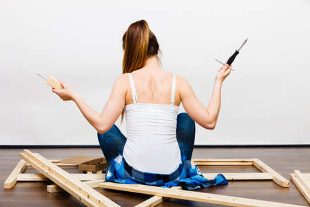 self assembly: Woman assembling wooden furniture using screwdriver. DIY enthusiast. Young girl doing home improvement. Rear back view. Stock Photo
