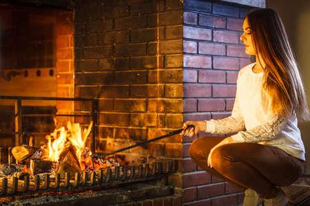 estufa: Mujer con atizador de hierro de fuego en la chimenea. Joven calefacción chica calentamiento y relajante. Invierno en casa.