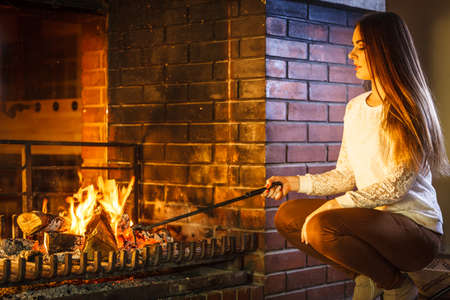 stove: Woman with fire iron poker at fireplace. Young girl heating warming up and relaxing. Winter at home.