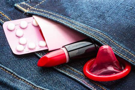 sex education: Healthcare medicine, contraception and birth control. Closeup oral contraceptive pills, condom and red lipstick in denim pocket.
