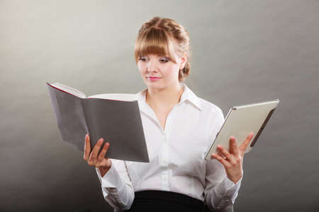 e book: Woman learning with ebook reader and book. Choice between modern educational technology and traditional way method. Girl holding digital tablet pc and textbook. Contemporary education.