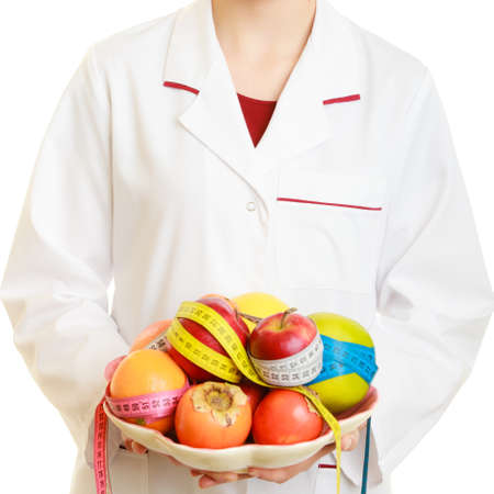 recommending: Closeup woman in white lab coat holding fruits and colorful measure tapes isolated. Doctor dietitian recommending healthy food. Dieting
