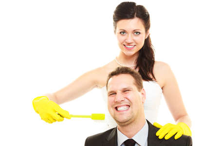 domination: Emancipation idea concept. Humorous funny wedding couple bride and groom. Woman brushing teeth of her man showing her domination and taking control. Isolated on white. Stock Photo