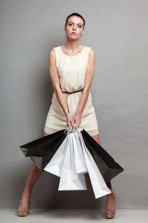 shopaholism: Woman in full length sale and retail time. Girl with black and white shopping bags in hands on grey background in studio.
