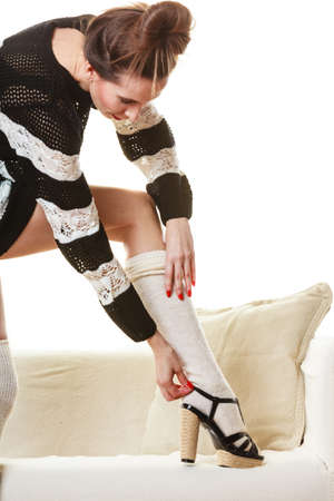 sweater girl: Fashionable woman legs. Girl in striped dress puts on woolen stockings indoor at home