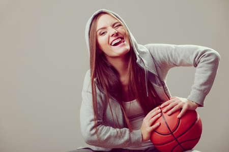 hooded sweatshirt: Funny sporty teenager girl wearing hooded sweatshirt holding basketball. Teen sport. Face expression.