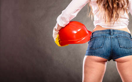 ass jeans: Closeup of structural engineer holding helmet. Woman grl working in man profession. Independent female.