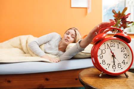 power nap: Exhausted woman waking up in bed turning off alarm clock. Young girl in the morning. Stock Photo
