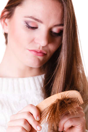 dissatisfied: Dissatisfied woman combing with brush and pulls at her long hair. Being unhappy for nice look in daily activity.
