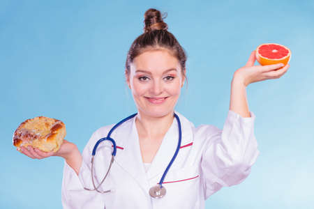 eating right: Happy dietitian nutritionist with sweet roll bun and grapefruit. Woman holding fruit and cake comparing junk and healthy food. Right eating nutrition concept. Stock Photo