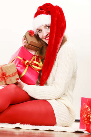 santa helper: Christmas winter happiness concept. Woman wearing santa helper hat with many presents red golden gift boxes