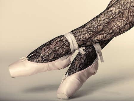 bailarina: hermosa bailarina de ballet de la mujer, que forma parte de las piernas del cuerpo en zapatos y medias de encaje negro foto de estudio sobre fondo gris
