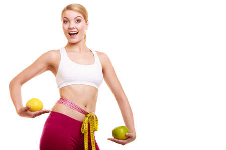 slim woman: Smiling young woman girl holding grapefruits measuring waist with tape measure. Slimming and dieting. Healthy lifestyle nutrition concept. Isolated on white. Stock Photo