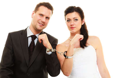 prisoner of love: Relationship in married couple. Bride and groom with handcuffs on their hands isolated on white.