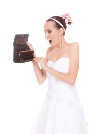 suprise: Surprised bride with empty wallet. Young girl holding purse looking for money cash. Wedding expenses costs, expenditure. Finance concept. Woman in white wedding dress isolated on white background. Stock Photo