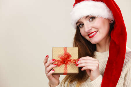 santa helper: Christmas winter happiness concept. Smiling latin woman wearing santa helper hat holding present gift box