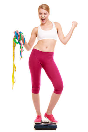 weight loss success: Slimming and weight loss success. Happy young woman girl measuring with tape measures on weighing scale clenching fists. Healthy lifestyle concept. Isolated on white. Stock Photo