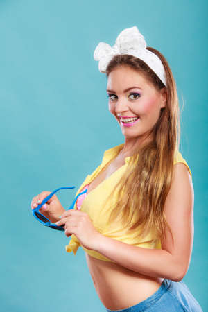 gorgeous: Portrait of happy smiling pretty pin up girl with hairband bow wearing heart shaped sunglasses. Attractive gorgeous young retro woman posing in studio on blue background.