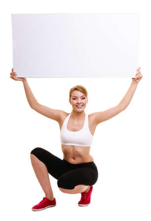 isolated sign: Fitness and health lifestyle advertisement. Young woman girl holding banner high up presenting blank empty ad copyspace isolated on white background. Stock Photo